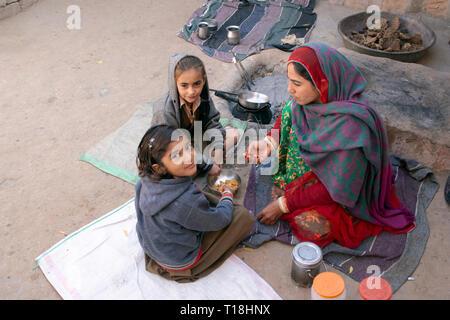 Two Bishnoi girls eat breakfast before walking to their village school. - Stock Image