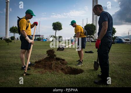 180824-N-UY653-034  BATUMI, Georgia (Aug. 24, 2018) Damage Controlman 1st Class Aaron Bean, left, and Lt. Zach Braida, assigned to the Arleigh Burke-class guided-missile destroyer USS Carney (DDG 64), dig a hole before planting a tree during a community relations event in Batumi, Georgia, Aug. 24, 2018. Carney, forward-deployed to Rota, Spain, is on its fifth patrol in the U.S. 6th Fleet area of operations in support of regional allies and partners as well as U.S. national security interests in Europe and Africa. (U.S. Navy photo by Mass Communication Specialist 1st Class Ryan U. Kledzik/Relea - Stock Image