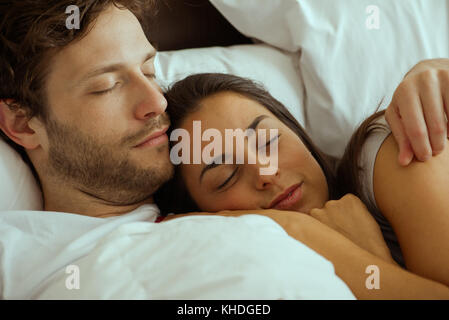 Couple resting and embracing in bed - Stock Image