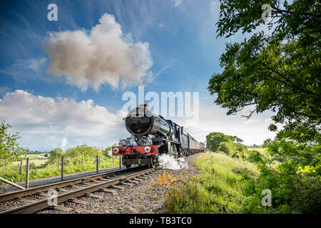 Vintage, British, steam locomotive, King Edward II approaching on the railway track, passing through rural countryside on a sunny spring afternoon. - Stock Image