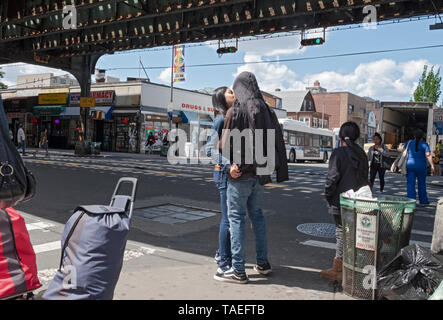 A busy street scene under the elevated subway with a couple kissing, pedestrians, luggage & trash. In Jackson Heights, Queens, New York City. - Stock Image