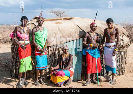 Five adult Samburu Maasai Men posing in front of a traditional manyatta hut in a village in Samburu, Kenya, East - Stock Image