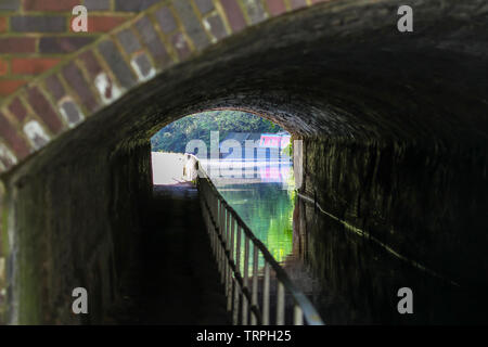 Landscape view looking through a dark, UK canal tunnel on bright sunny day. Detailed tunnel brickwork interior & outside sun reflected in canal water. - Stock Image