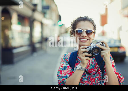 Portrait smiling young female tourist in sunglasses photographing with camera on urban street - Stock Image