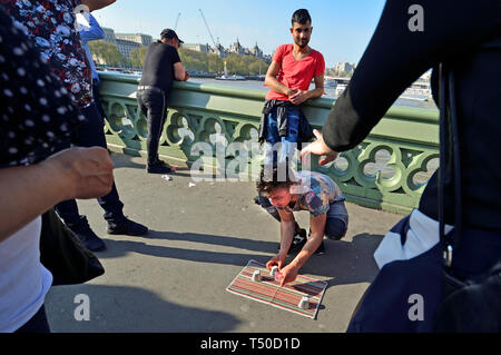 London, UK. 19th Apr 2019. On a busy Good Friday Bank Holiday, the pavement of Westminster Bridge is almost blocked by more than 10 illegal games of the 3 Cups Trick or Cup and Ball, designed to relieve tourists of their money by having stooges apparently win large sums FIRST. Credit: PjrFoto/Alamy Live News - Stock Image
