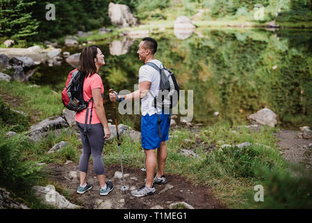 Couple hiking at lake in woods - Stock Image