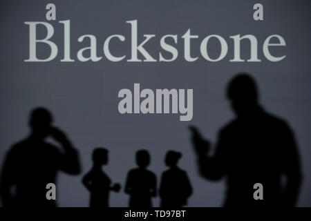 The Blackstone logo is seen on an LED screen in the background while a silhouetted person uses a smartphone in the foreground (Editorial use only) - Stock Image