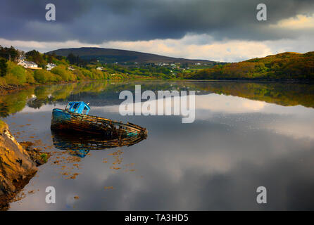 An old inshore fishing boat lying in the waters of Teelin Bay near Slieve League, County Donegal, Ireland - Stock Image