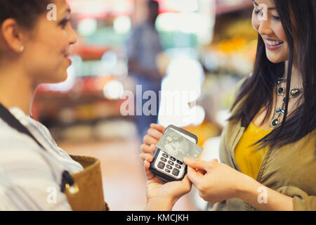 Female customer with credit card using contactless payment in store - Stock Image