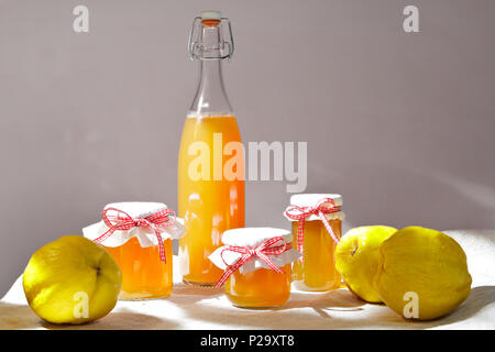 Homemade quince jelly and Juice in a bottle and glass jars with quinces on a linen tablecloth in bright sunshine in front of a neutral background. - Stock Image