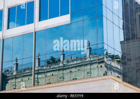 Reflection of a historic building in the modern glass building found in downtown Havana. - Stock Image