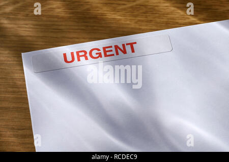 An Urgent sticker on a white envelope - Stock Image