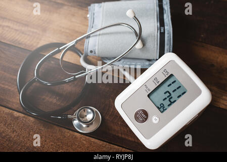 Stethoscope and Sphygmomanometer an electronic blood pressure monitor on a wooden table. concept of health and medical - Stock Image