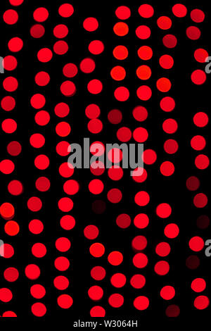 Unfocused abstract red bokeh on black background. defocused and blurred many round light. - Stock Image