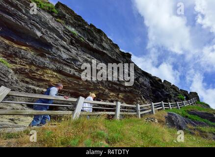 Tourists walking the steep climb up to Tintagel Castle,Cornwall,England,UK - Stock Image