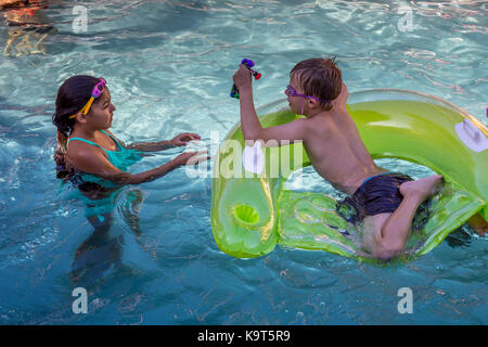 girl and boy, children, playing in pool, swimming pool, freshwater swimming pool, pool party, Castro Valley, Alameda - Stock Image
