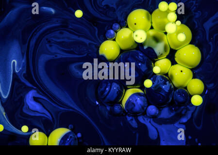 Yellow drops of oil suspended in blue chemical oil slick creating an abstract between nature and a polluted hazardous - Stock Image