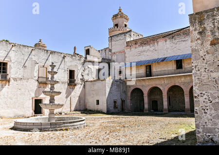 A secondary courtyard looking toward the front at the fading Hacienda de Jaral de Berrio in Jaral de Berrios, Guanajuato, Mexico. The abandoned Jaral de Berrio hacienda was once the largest in Mexico and housed over 6,000 people on the property and is credited with creating Mescal. - Stock Image