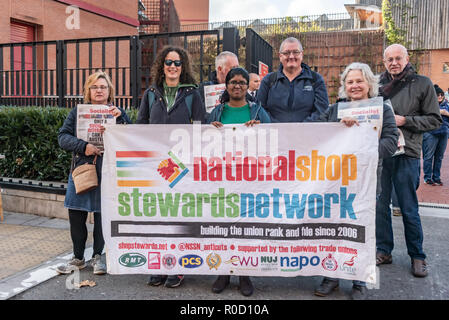 London, UK. 3rd November 2018. People pose with the NSSN (National Shop Stewards Network) banner as they gather at the British Library for a march and rally against cuts in library services, which are a vital part of our cultural services, especially for working class schoolchildren and young people. Over 100 libraries closed in 2017 and we need the Government to take action to stop and reverse library cuts. The event in support of libraries, museums and cultural services was organised by Unison and supported by PCS and Unite. Credit: Peter Marshall/Alamy Live News - Stock Image