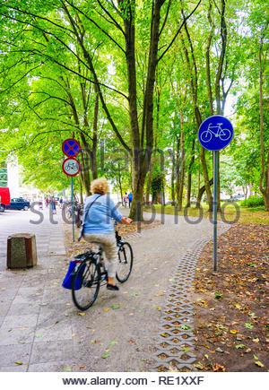 Kolobrzeg, Poland - August 10, 2018: Woman riding a bicycle on a path at a park - Stock Image