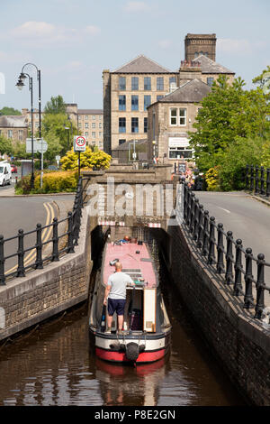 Narrowboat on the Huddersfield Narrow Canal passing through tunnel under road, Slaithwaite, West Yorkshire - Stock Image