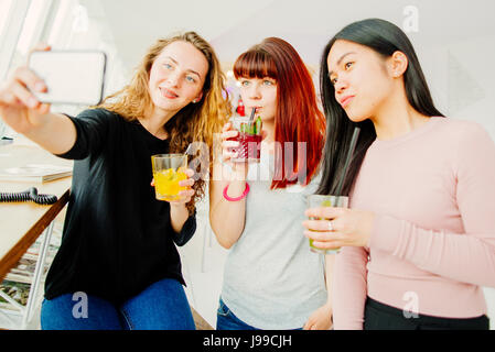 Three young girlfriends taking selfie - Stock Image