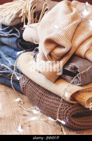 stack of of warm clothes, stack of jeans and a garland on the old wooden background - Stock Image