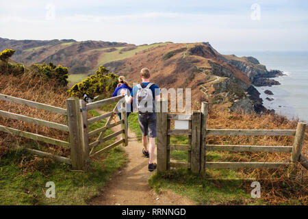 Two people walking on the South West Coast Path and Tarka Trail towards Bull Point from Lee Bay, Ilfracombe, North Devon, England, UK, Britain - Stock Image