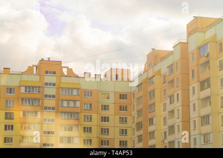 Modern multi-storey brick house yellow, the inner corner of a residential building with balconies, against the sky with clouds, bottom view. - Stock Image