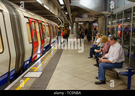 Passengers sit and wait on a bench on the platform at Westminster London Underground Station as other passengers board a train. - Stock Image