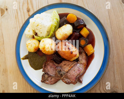 English lunch  dinner meal lamb chops roast potatoes cauliflower roasted carrots red wine gravy and mint sauce blue edge white plate on a wooden table - Stock Image