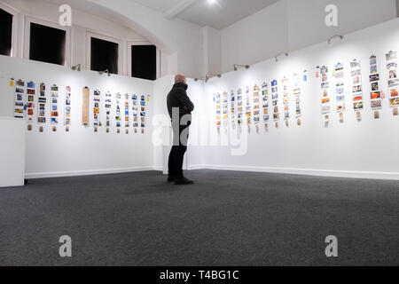 One man looking at an exhibition of small photographs from the Aberystwyth Photomarathon / Ffotomarathon  competition 2018, in a small whire walled art  gallery in the Old College building, Wales UK - Stock Image