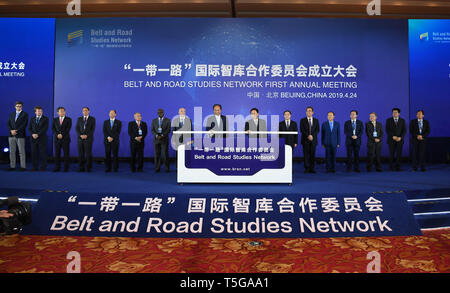 Beijing, China. 24th Apr, 2019. Cai Mingzhao (L, center), president of Xinhua News Agency, chairman of Xinhua Institute and chairperson of an initiators council of the Belt and Road Studies Network (BRSN), witnesses with other guests the launching of the BRSN's official website, www.brsn.net, in Beijing, capital of China, April 24, 2019. The Belt and Road Studies Network (BRSN), co-initiated by Xinhua Institute and 15 other think tanks, was inaugurated in Beijing Wednesday. Credit: Jin Liangkuai/Xinhua/Alamy Live News - Stock Image
