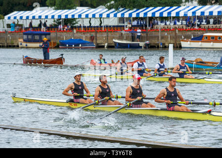 Two coxless four rowing boats and crews race to the finish line on the River Thames at Henley Royal Regatta, Henley on Thames, Oxfordshire, UK - Stock Image