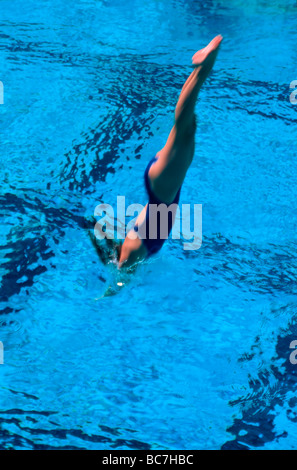 Woman Dives into Swimming Pool - Stock Image
