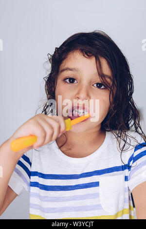 vertical portrait of a little girl brushing her teeth in the bathroom in the morning after taking a shower, kids hygiene concept, copy space for text - Stock Image