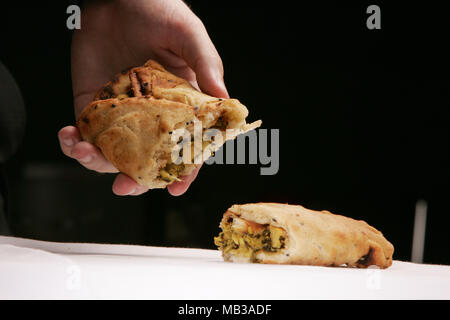 A pasty food snack opened in half to see filling - Stock Image