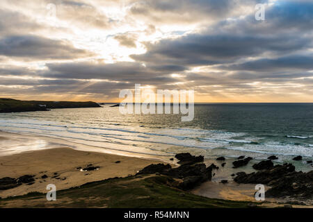 Just before sunset over a stormy Fistral Beach with surfers, Newquay, Cornwall, UK - Stock Image