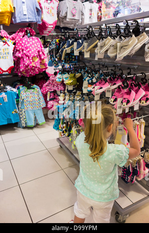 A young girl looking at shoes in a shop. - Stock Image