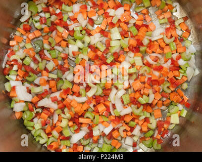 Diced vegetables frying in the bottom of a pot. - Stock Image