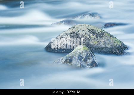 granite boulders surrounded by the flow patterns of the River Dart on Dartmoor - below Dartmeet - Stock Image