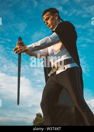 Brown-haired man with elf ears, carrying a sword in his hands. - Stock Image
