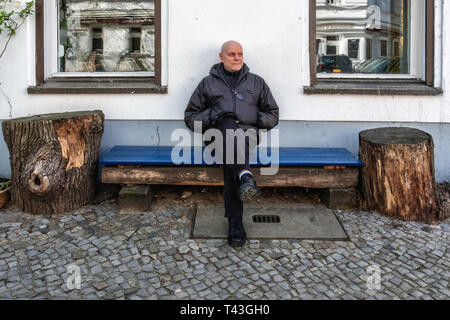 Berlin Mitte. Elderly pensioner sits on bench on urban pavement. Senior man resting, unhurried, not in a rush - Stock Image