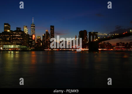 NEW YORK, NY - JULY 03: Financial District, Lower Manhattan, and Brooklyn Bridge skyline after sunset as seen from Brooklyn Bridge Park, Brooklyn on J - Stock Image