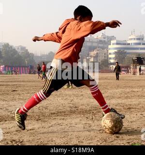 Boy playing football, Kathmandu - Stock Image