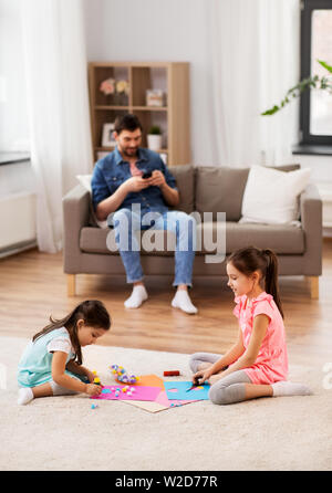 happy sisters doing arts and crafts at home - Stock Image