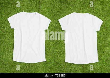 Front and back of white empty T-shirt on grass background. Horizontal view. - Stock Image