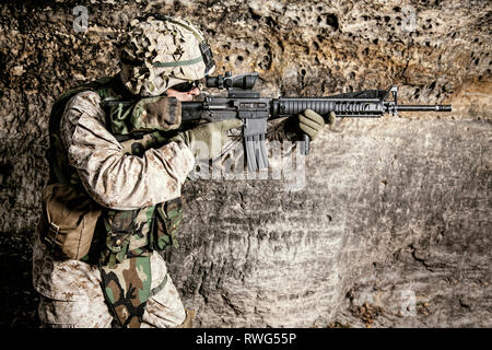 U.S. Marine Corps soldier in action among the rocks. - Stock Image