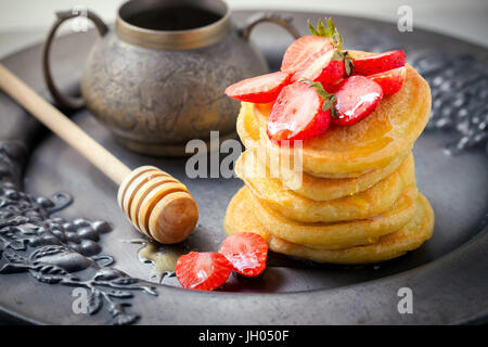 Stack of sweet pancakes with strawberry and honey. Gluten free flour. - Stock Image