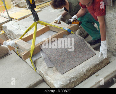 Stonemasons Can Henne (L) and Franz Guenther (R) fit a stone panel into its place during reconstruction works for - Stock Image